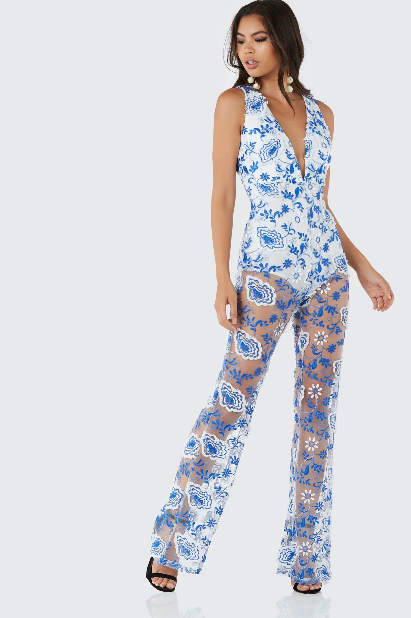 Stunning sleeveless jumpsuit with plunging V-neckline. Bodysuit lining with mesh overlay and bold embroidery throughout. Cut out in back with button and hidden zip closure.