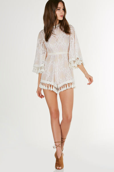 Bell sleeve lace romper with hints of peach, pink and white adorned with tassle trimming. Has keyhole back detail, button closure at back of neck, and invisible zipper closure at bottom. Nude lining with adustable inner straps.