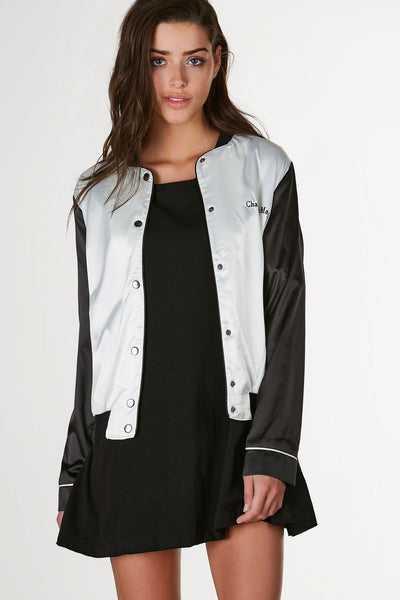 Lightweight bomber with chic satin finish. Contrast ribbed hem with snap button closure and graphic stitched in front.