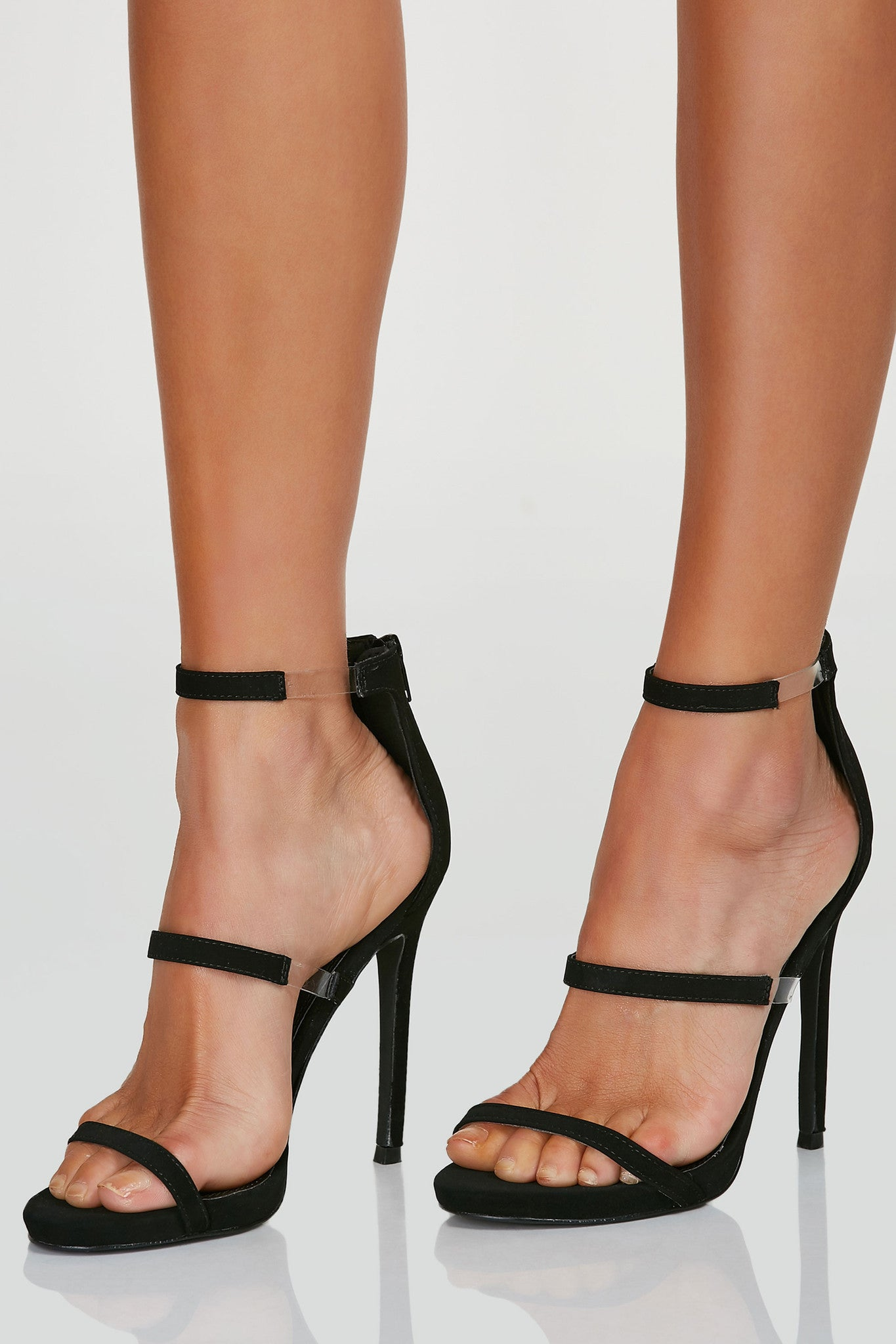 Sleek pair of three strap heels with contrast clear bands on each side. Back zip closure with slightly rounded toe finish.