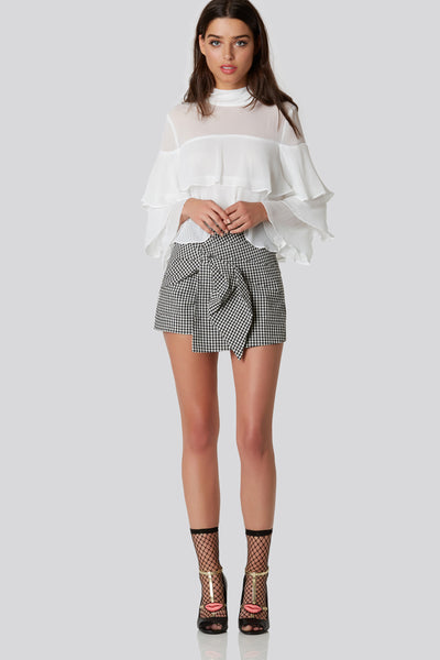 Chic pair of high rise skort with stylish wrap over design with knot detailing in front. Timeless checkered print throughout with hidden side zip closure.