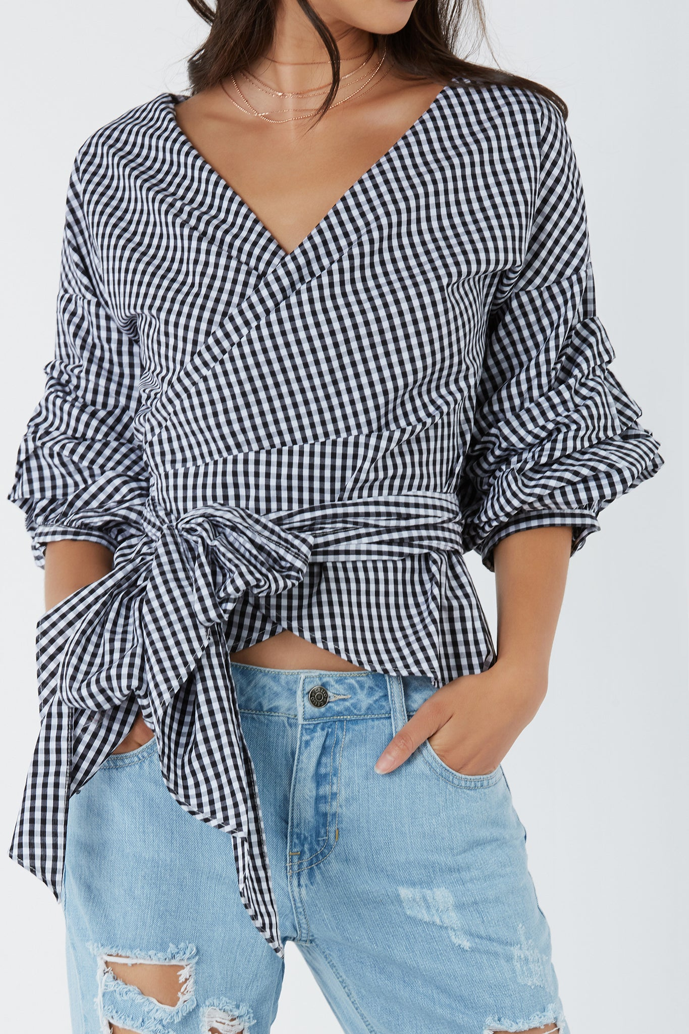 Bold checkered top with chic V-neckline. Wrap front closure with structured ruched sleeves.