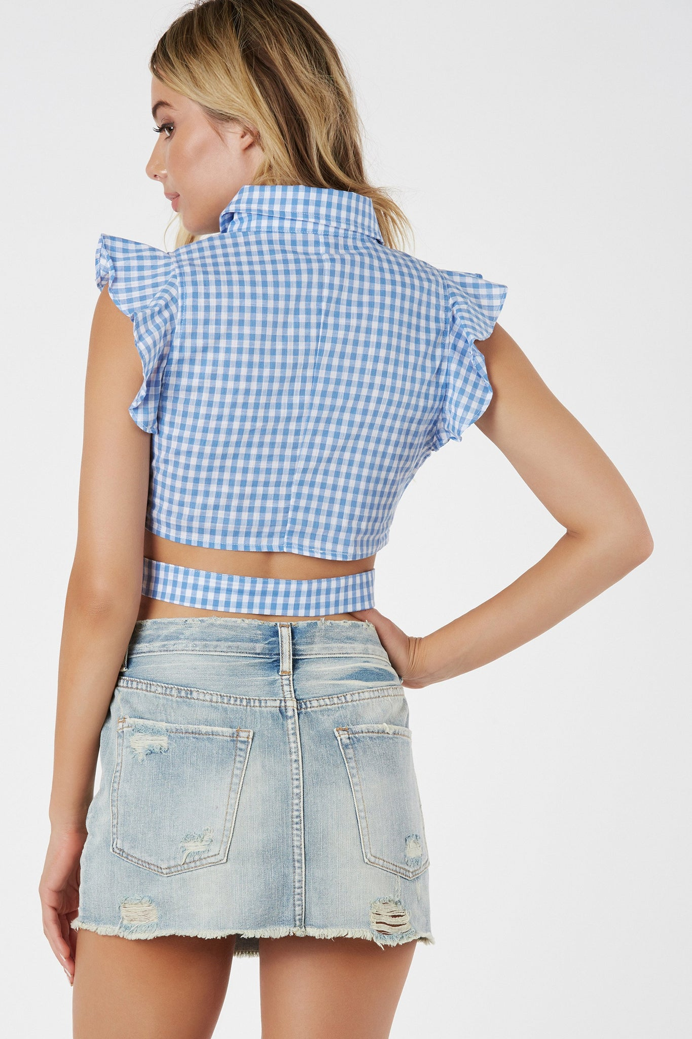 Flirty collared button down top with ruffle trim detailing. Checkered print with V-shape cut out and cropped hem finish.