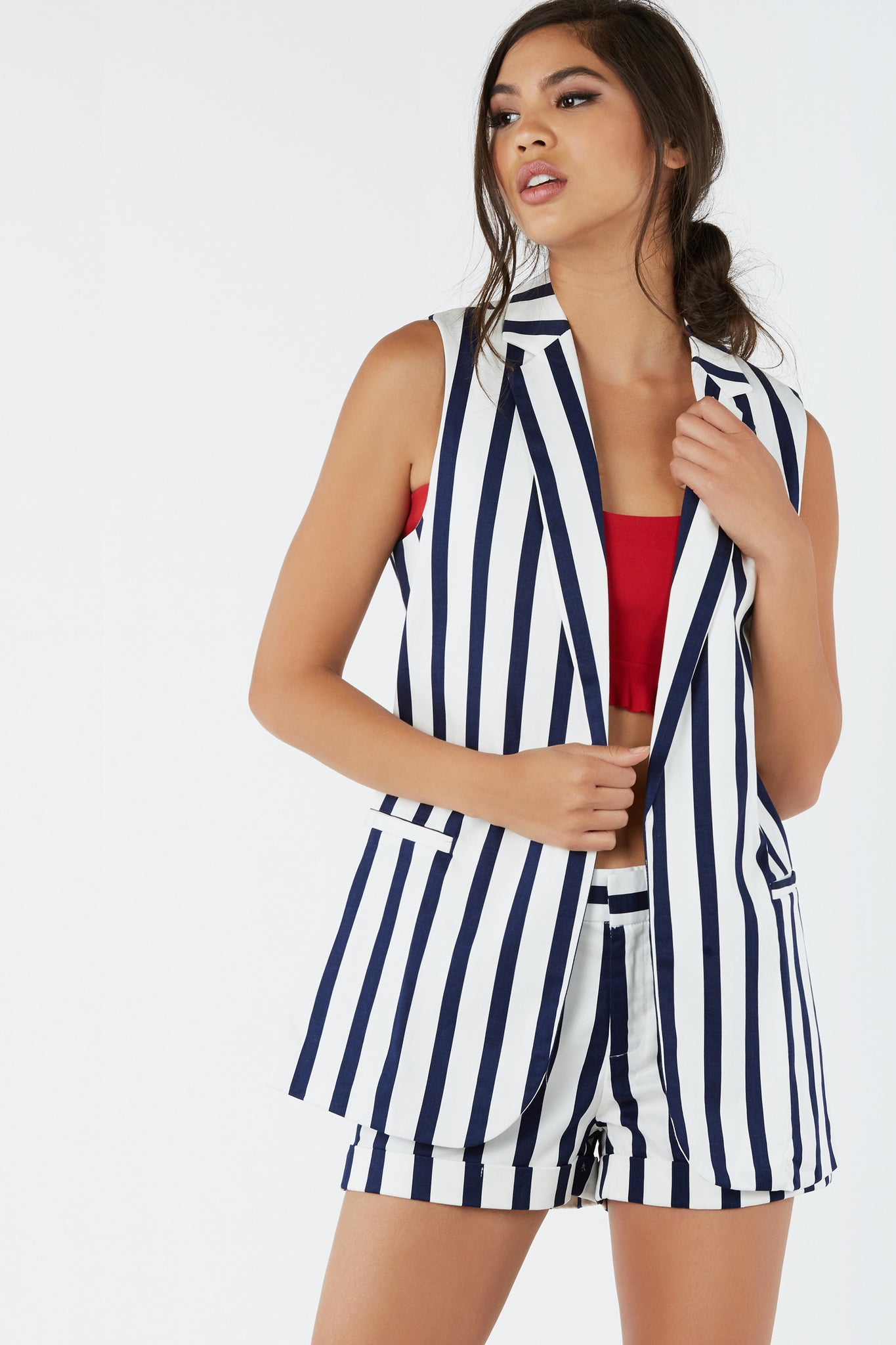 Sleeveless longline blazer with crisp collars and open front design. Faux pocket detailing with bold stripe patterns throughout.