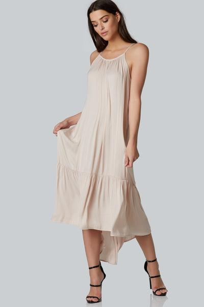 Sleeveless maxi dress with high neckline. Ruffle bottom hem detailing with tied straped back.