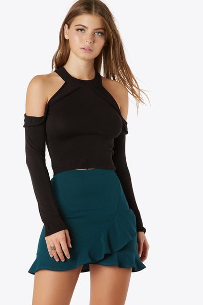 Long sleeve knit top with ruffled shoulder cut outs. Features high neckline and ribbed waistband.