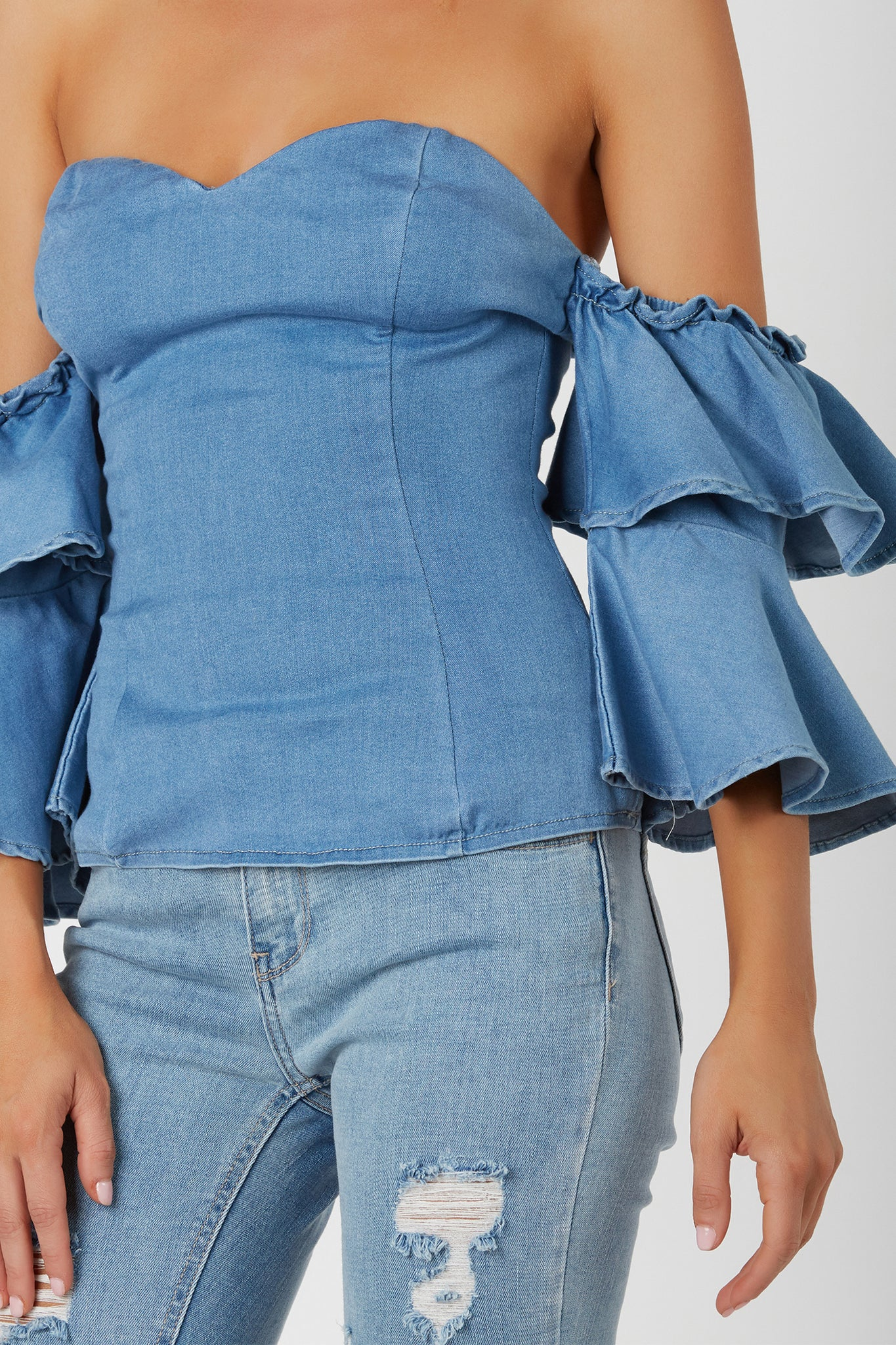Flirty off shoulder top with chic denim finish. Sweetheart neckline with fun ruffled sleeves.