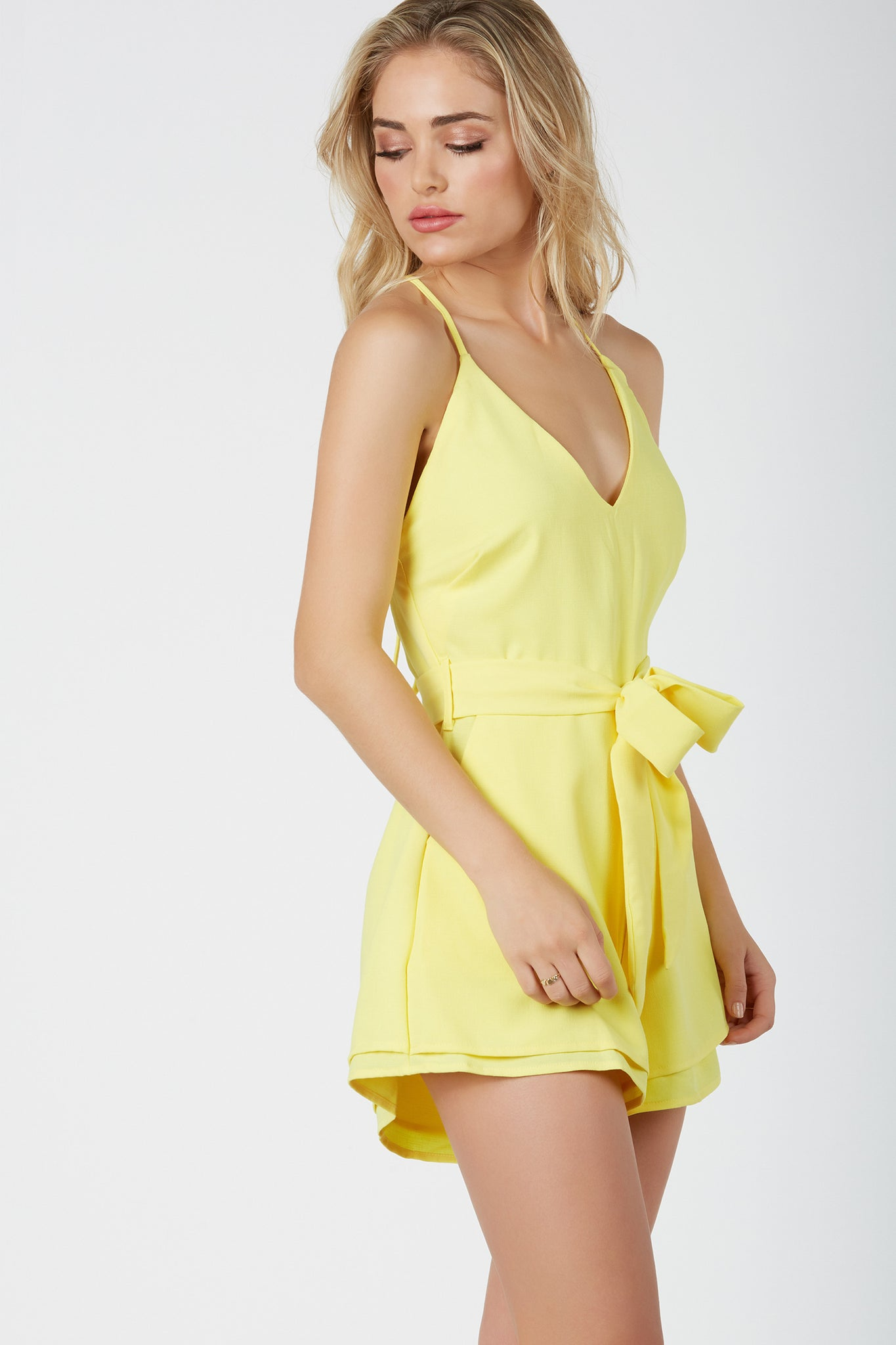 Chic halter romper with side pockets and tiered hem. Open back with ties for closure.