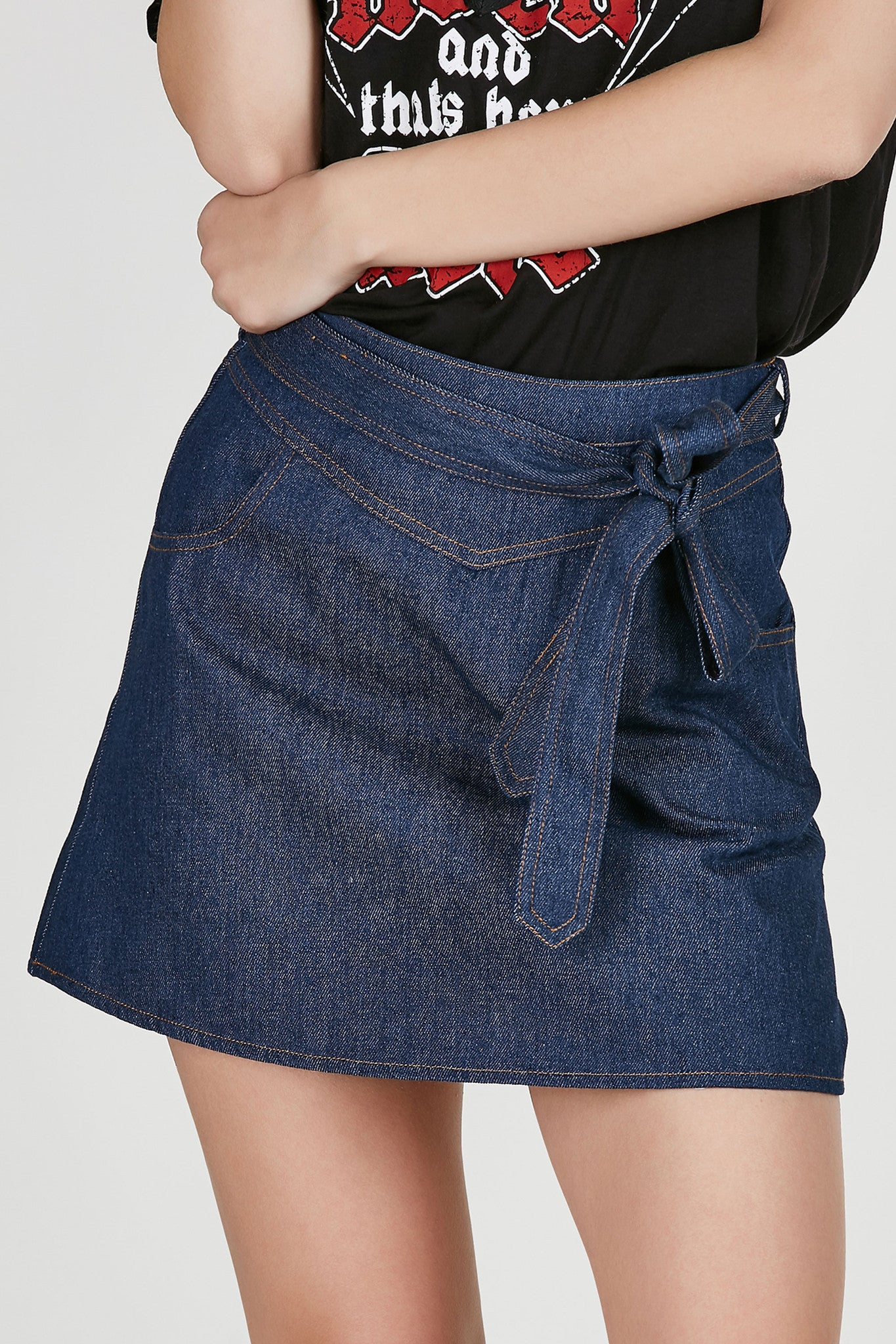 High rise denim mini skirt with tie at waist for added detail. Two pockets with hidden zip closure in back. Comfortable fit with A-line hem.
