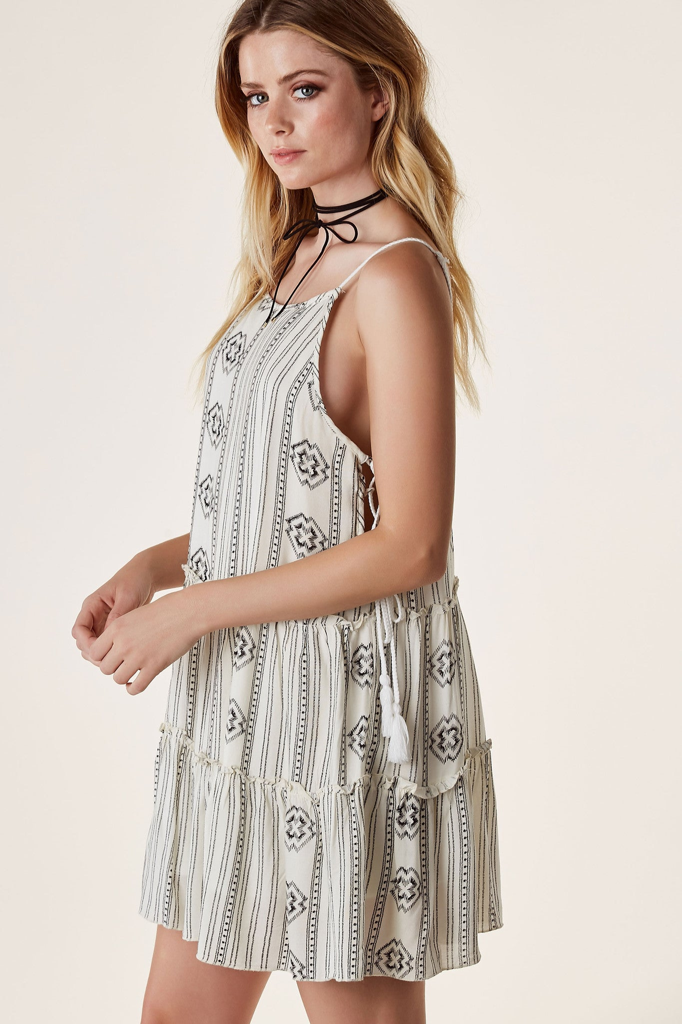 Flowy sleeveless printed dress with braided straps and lace up detailing on each side.