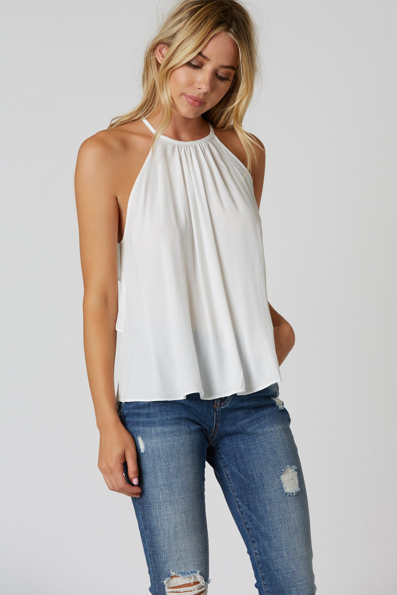 High neck sleeveless chiffon top with flowy A-line hem. Ruffled back with buttons for closure.