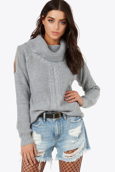 Stay warm in this cowl neck top with cable knit accents. Features cut outs on sleeves and rib knit hem.