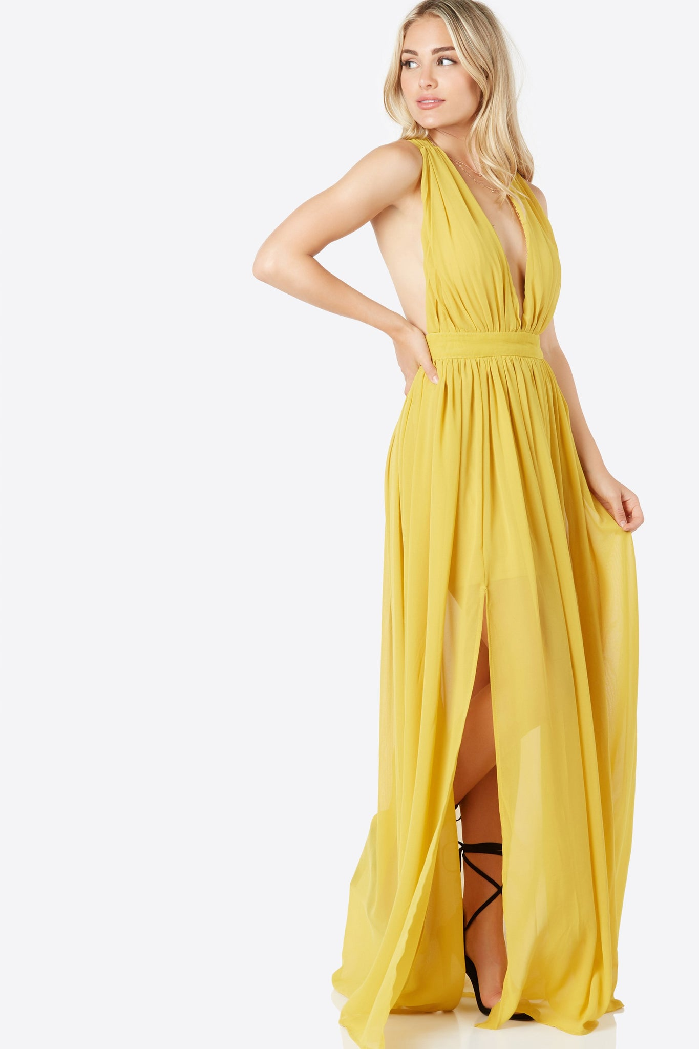 Stunning chiffon maxi dress with plunging neckline. Padded bust with flowy hem and slit detailing. Twisted strap design in back with hidden zip closure.