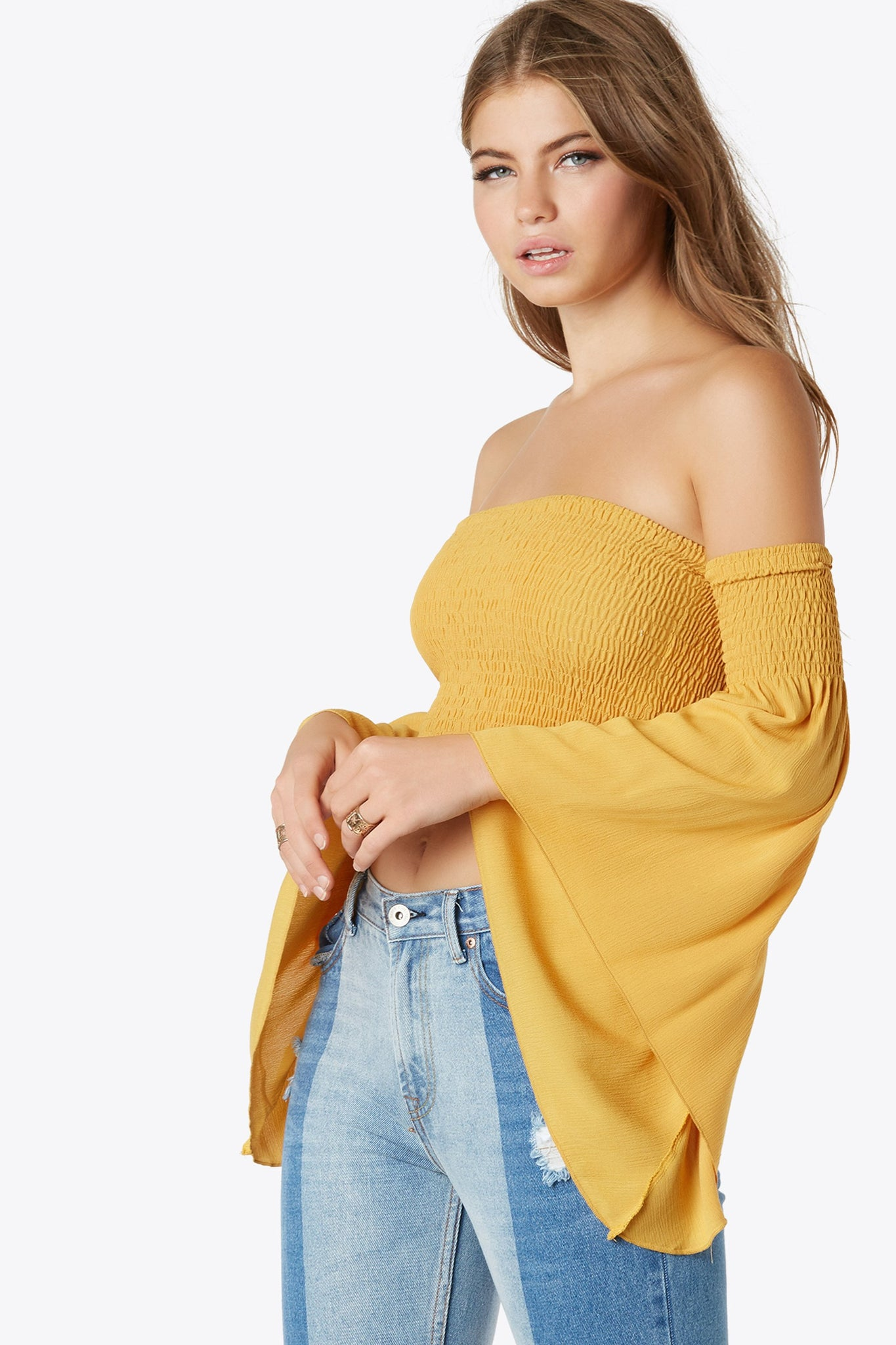 Smocked off shoulder crop top. Features flowy angel sleeves.