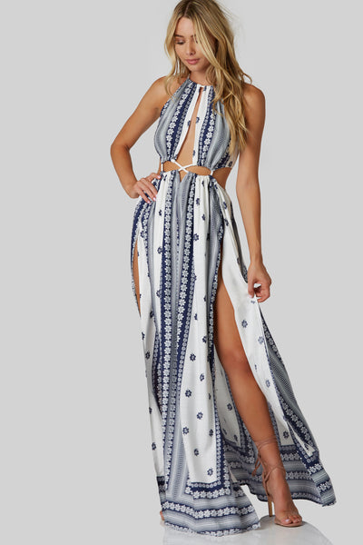 Stunning sleeveless maxi dress with high neckline with ties for closure. Cut out design with roped detailing. Colorful patterns throughout with flowy side slit hem.
