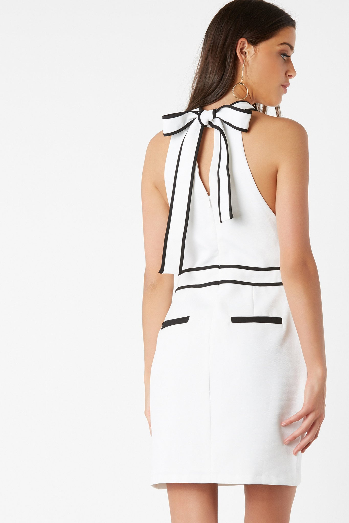 Sleeveless mock neck dress with bold piping for added detail. Long strap and faux pocket detailing in back.