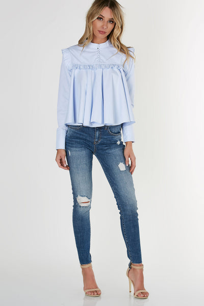 Mock neck long sleeve blouse with ruffle detailing and boxy fit. Long cuffed sleeves with A-line hem.