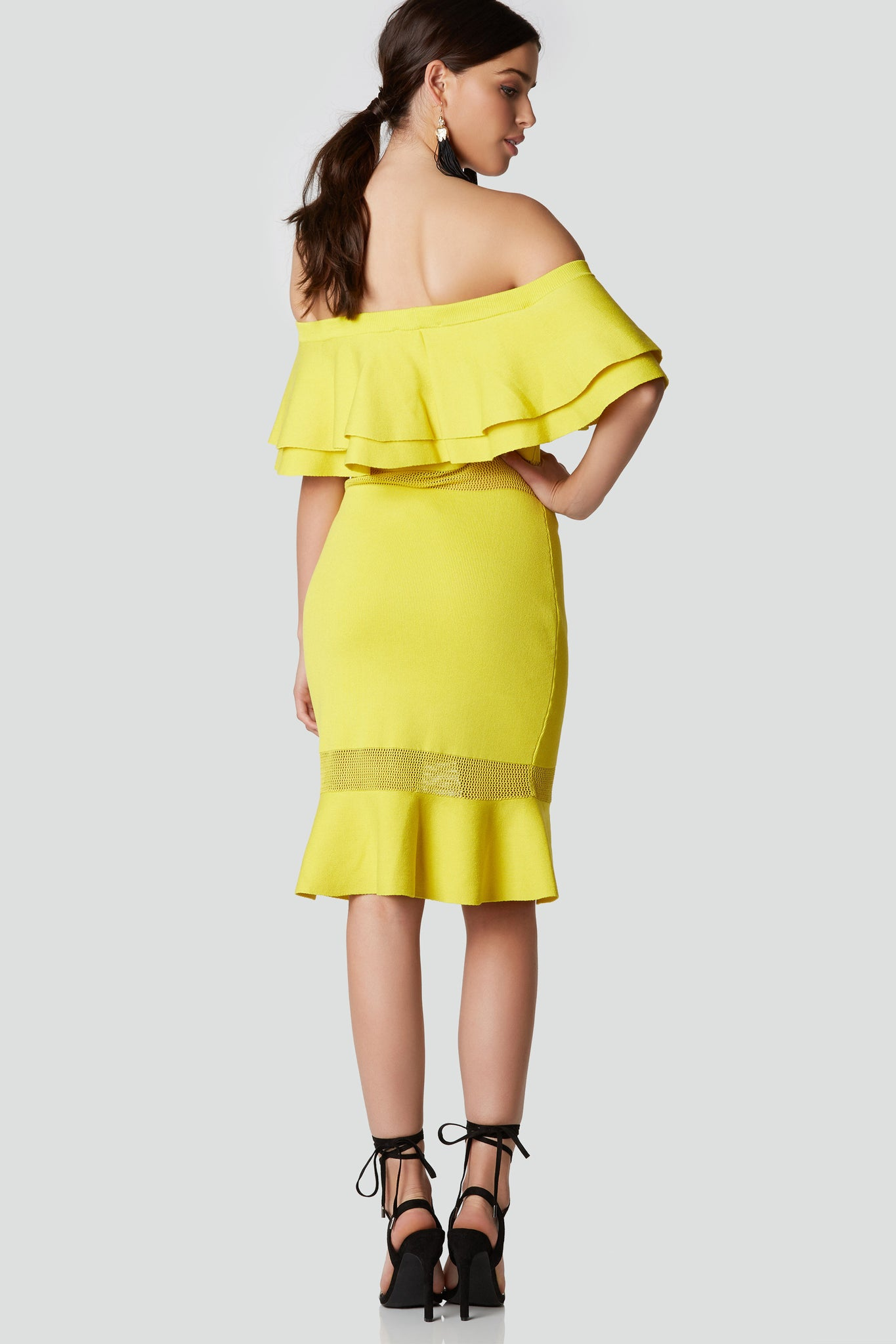 Chic off shoulder midi dress with tiered ruffle design and peek-a-boo knit panel detailing. Bodycon fit with flared hem finish.