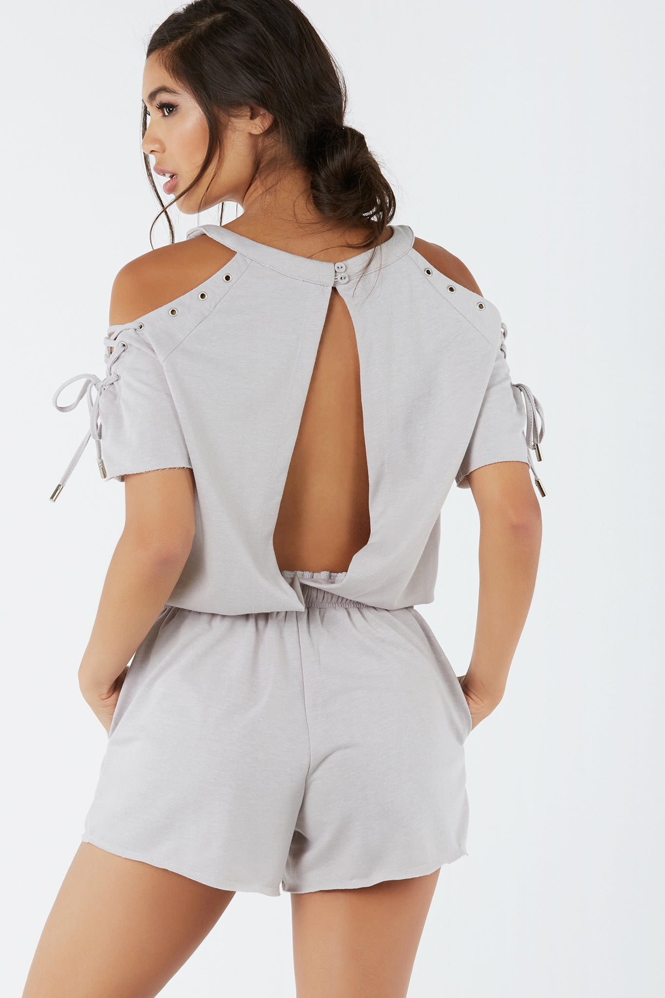 Soft cold shoulder romper with trendy cut outs. Eyelet detailing with lace up design at shoulder. Side pockets with drawstring at waist.