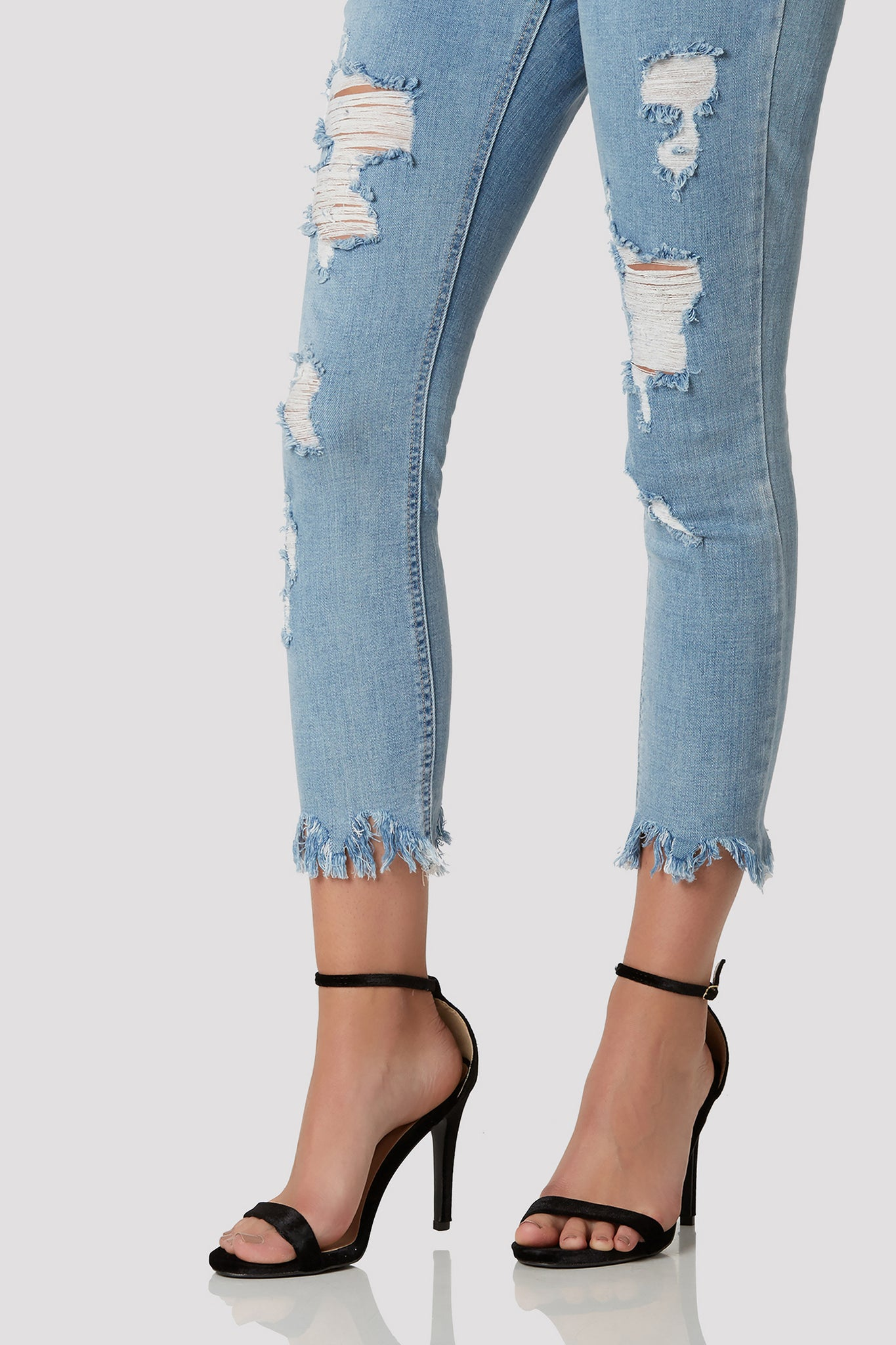 Trendy mid rise skinnies with distressing in front and uneven hem with frayed detailing.