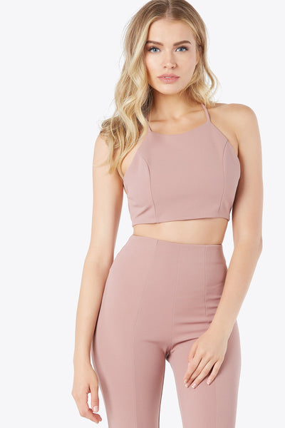 Thin strapped crop top with criss-cross back detailing. Adjustable tie closure.