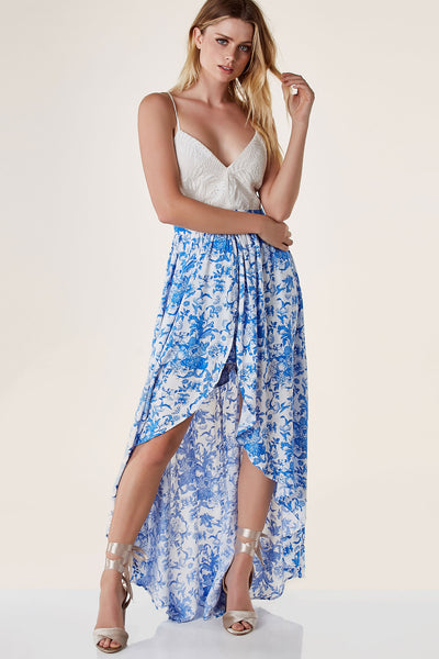 Sleeveless maxi romper with V-neckline and contrast crochet design at top. Floral printed bottoms with flowy overlay. Open back with lace up closure.