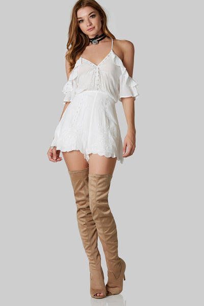 Flirty ruffled sleeve romper with cold shoulder design and embroidery in front. Scallop hem with cut out in back and hidden zip closure.