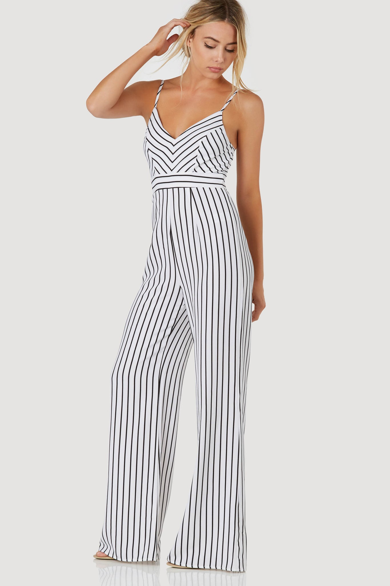 Chic sleeveless jumpsuit with classic V-neckline and stripe patterns throughout. Relaxed fit with back zip closure.