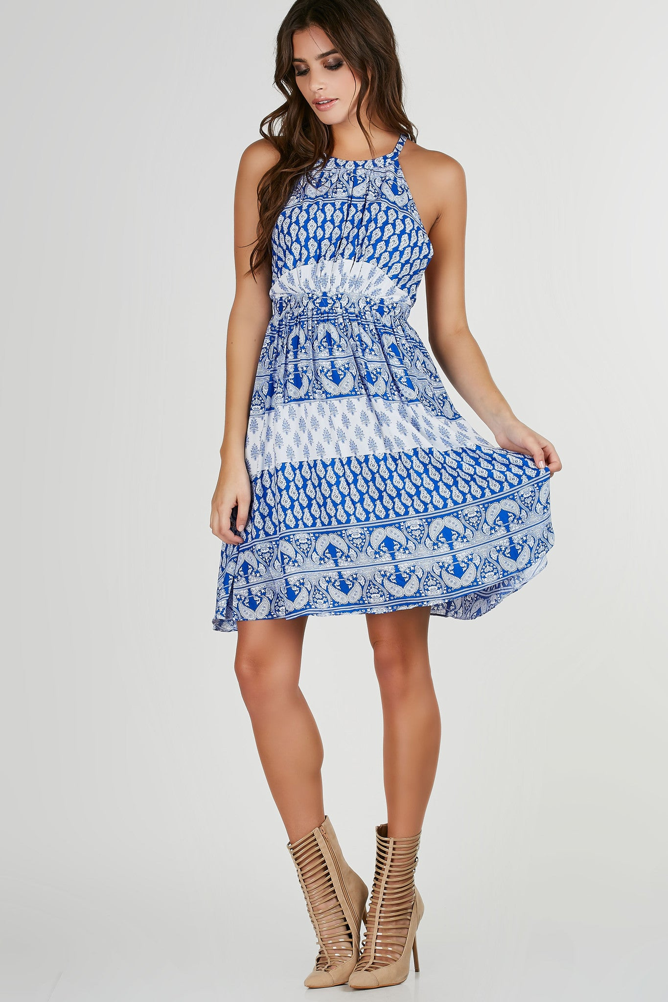 High neck sleeveless dress with intricate paisley prints throughout. Open back with strap detailing and flared hem.