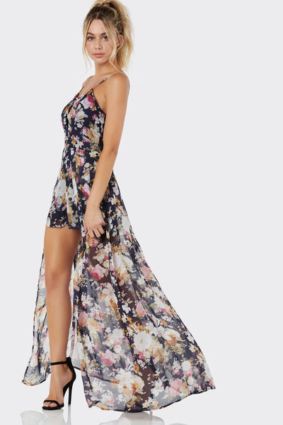 Stunning sleeveless chiffon romper with deep V-neckline and strappy design. Flowy maxi overlay with back zip closure.