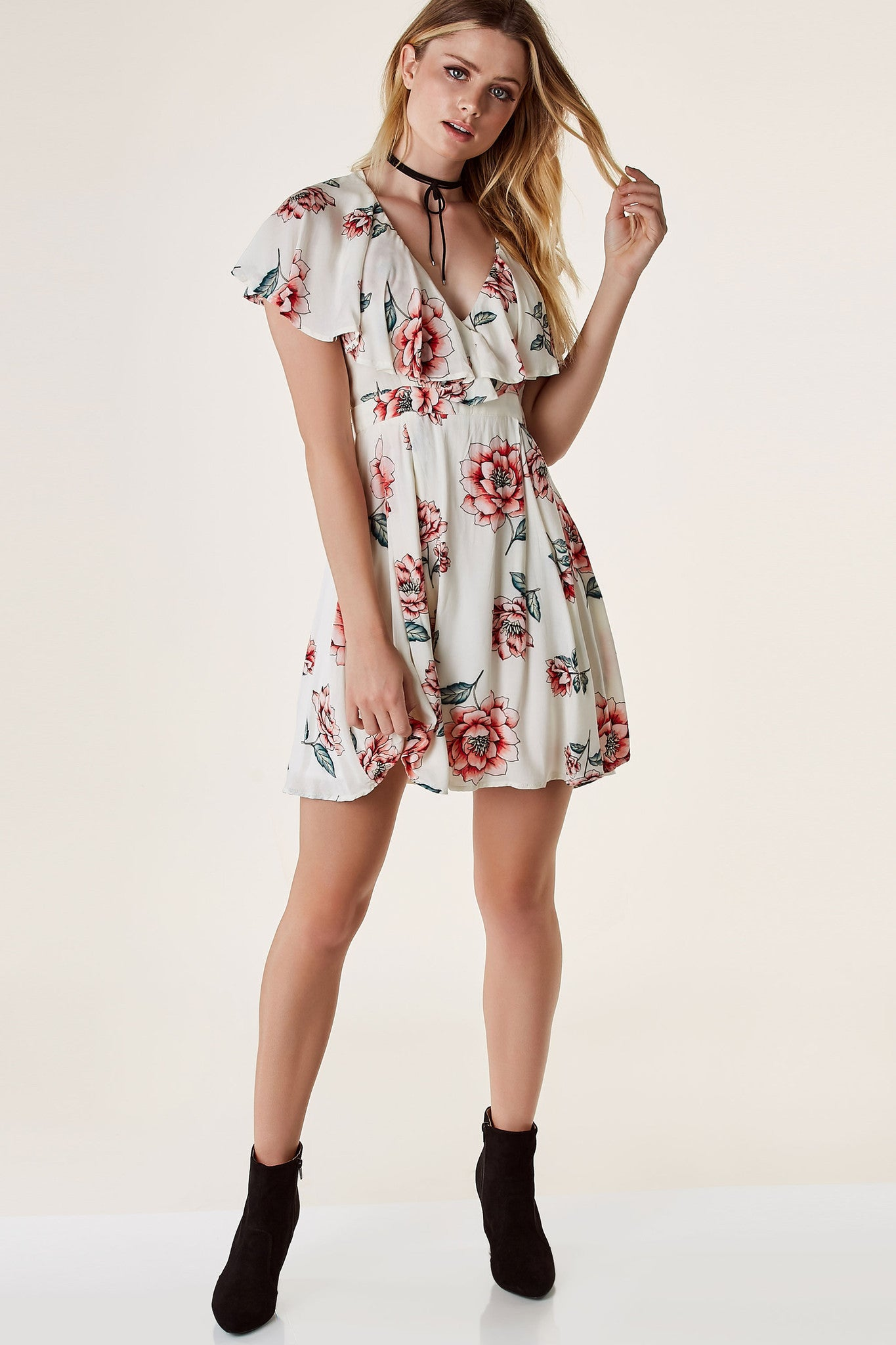 Flirty overlap V-neck dress with ruffle tier design and cap sleeves. A-line hem with cut out in back with ties and hidden zip closure.