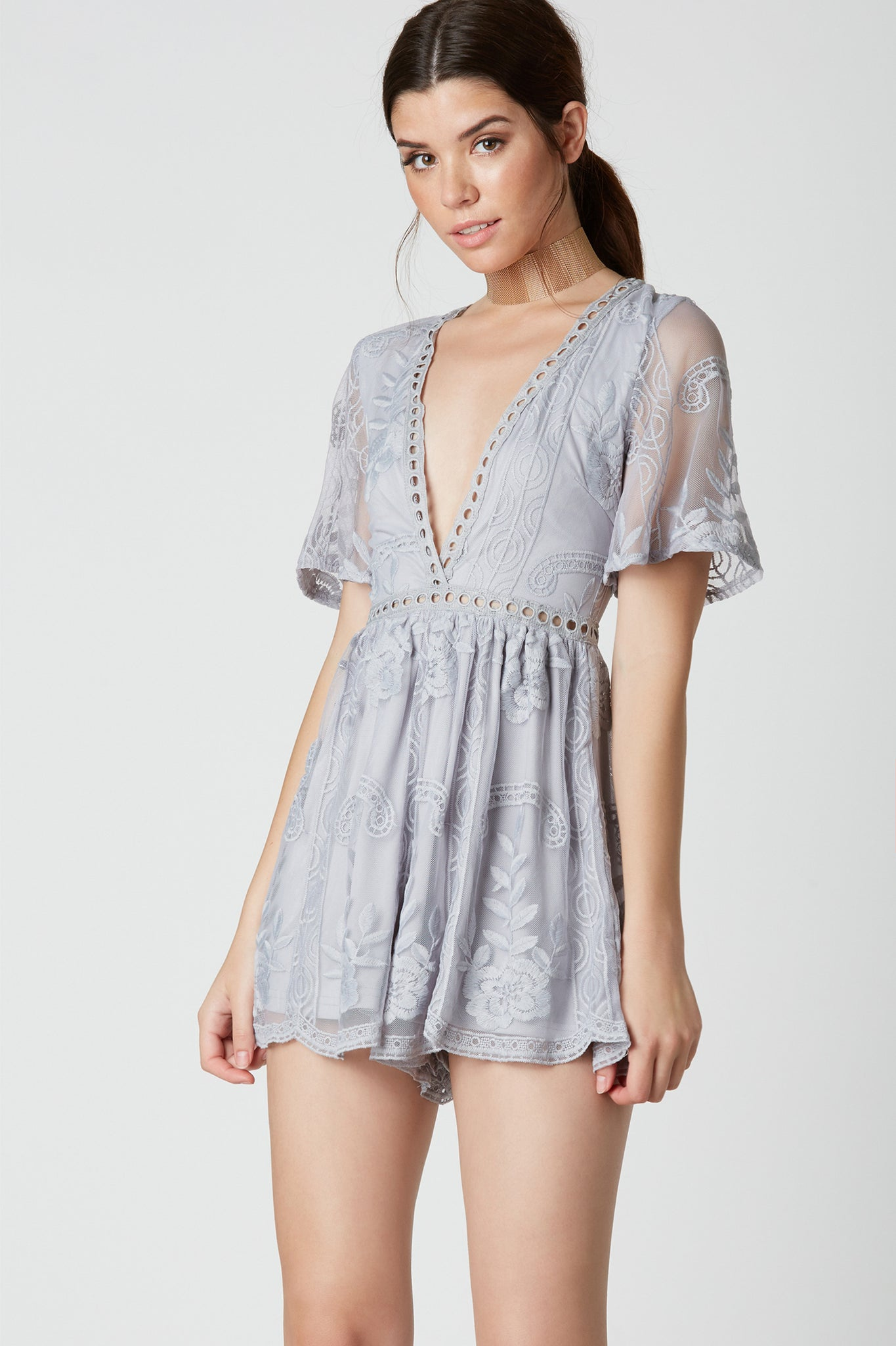 Stunning short sleeve romper with deep V-neckling and peek-a-boo crochet panel detailing. Fully lining with mesh overlay and intricate embroidery throughout. Scalloped hem and hidden back zip closure.