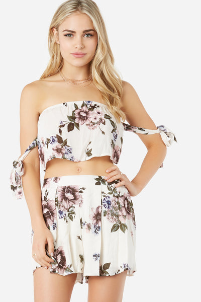 Off shoulder crop top with flowy fit. Floral print throughout with tie up sleeves and curved hem finish.