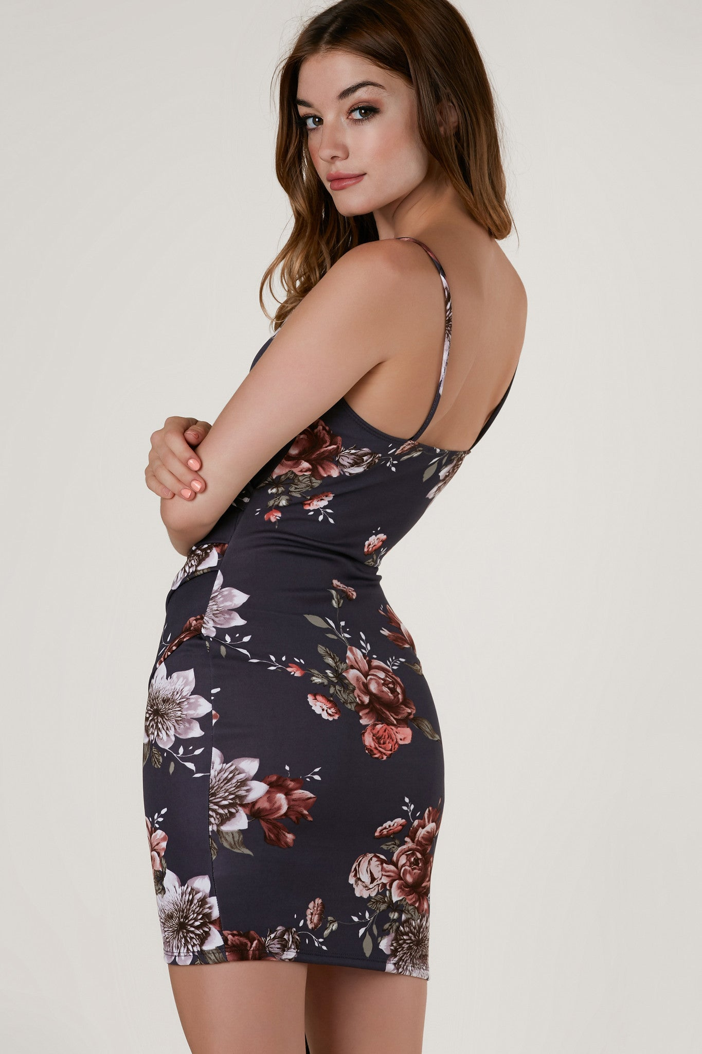 Sleeveless asymmetrical dress with overlap V-neckline and envelope style hem. Floral print throughout with ruching on one side for a flattering fit.