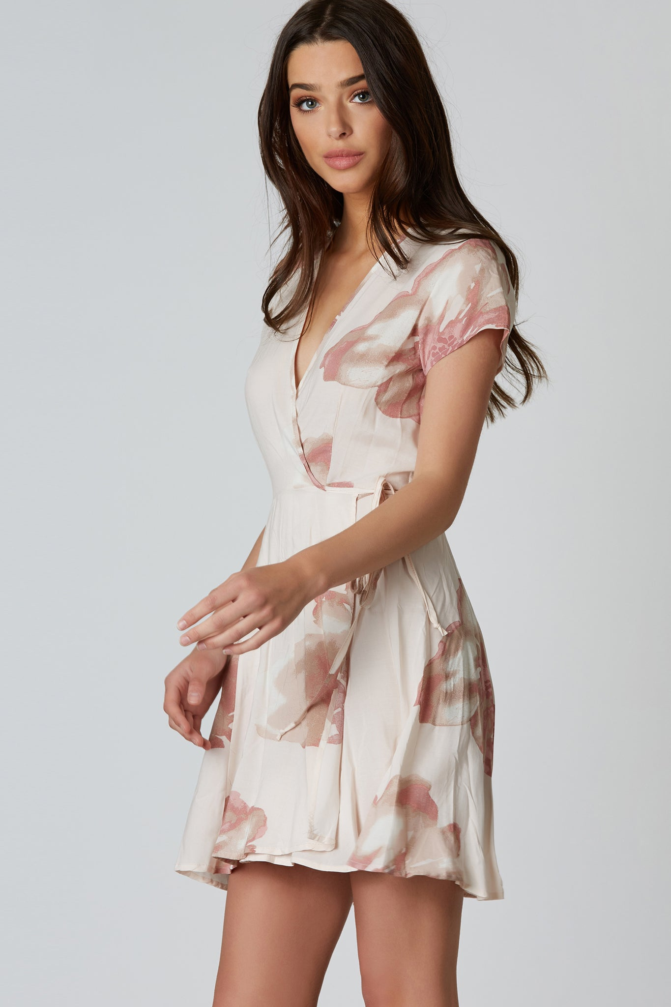 Chic collared mini dress with floral patterns throughout. Open front with wrap closure that ties on one side.