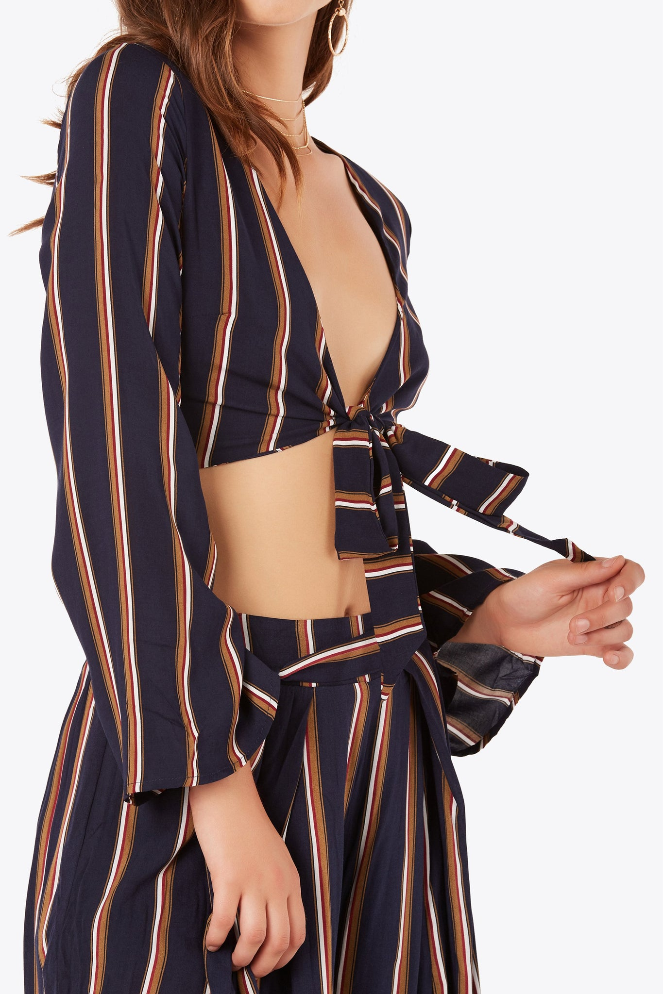 Long sleeev crop top with colorblock stripes printed throughout. Wide V-neckline with front tie closure.