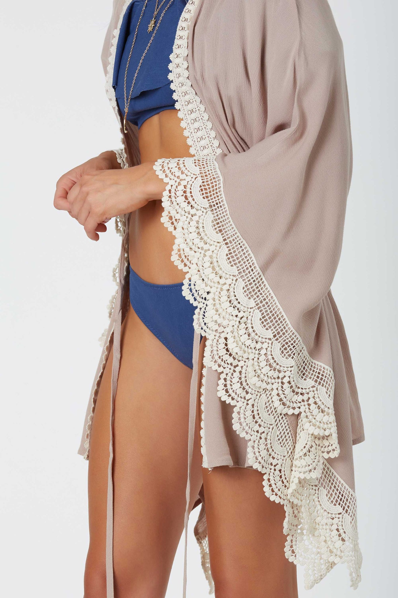 Boho-chic open front kimono with intricate crochet trim detailing. Boxy sleeves with center tie for closure.