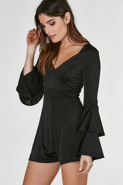 Deep V-neck romper made of smooth, slinky material with flattering fit. Long sleeves with tiered ruffle design. A-line hem and button closure with key hole cut out in back.