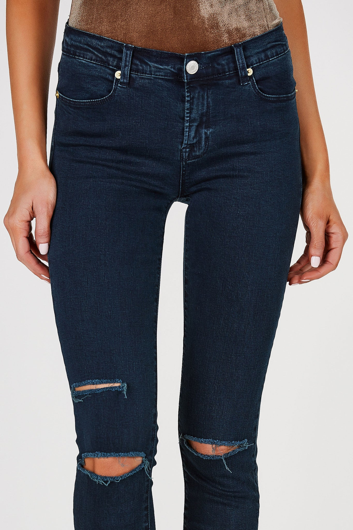 Mid rise skinny jeans in a deep wash. Distressing at knees with raw hem finish.