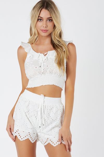 Flirty crop top with ruffle trim detailing. Floral embroidery throughout with elasticized hem finish.