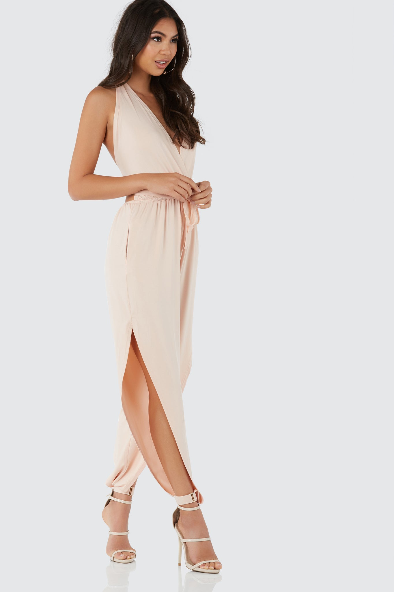 Slinky halter jumpsuit with sexy open back and bold slits on each leg. Buckle detailing with contrast mesh ties for closure.