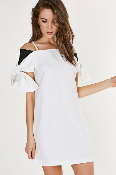 Chic cold shoulder tunic dress with boxy fit. Colorblock design with bows on each sleeve and back zip closure.