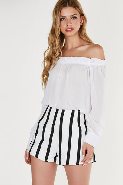 Flirty off shoulder blouse made of lightweight chiffon material. Ruffle trim at neckline with cuffed sleeves and curved hem.