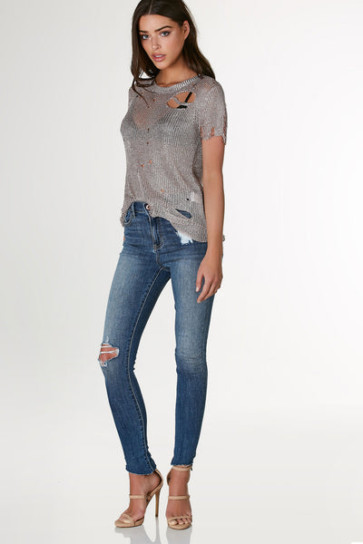 Stylish short sleeve top with crew neckline and distressing throughout. Metallic knit material with relaxed fit.