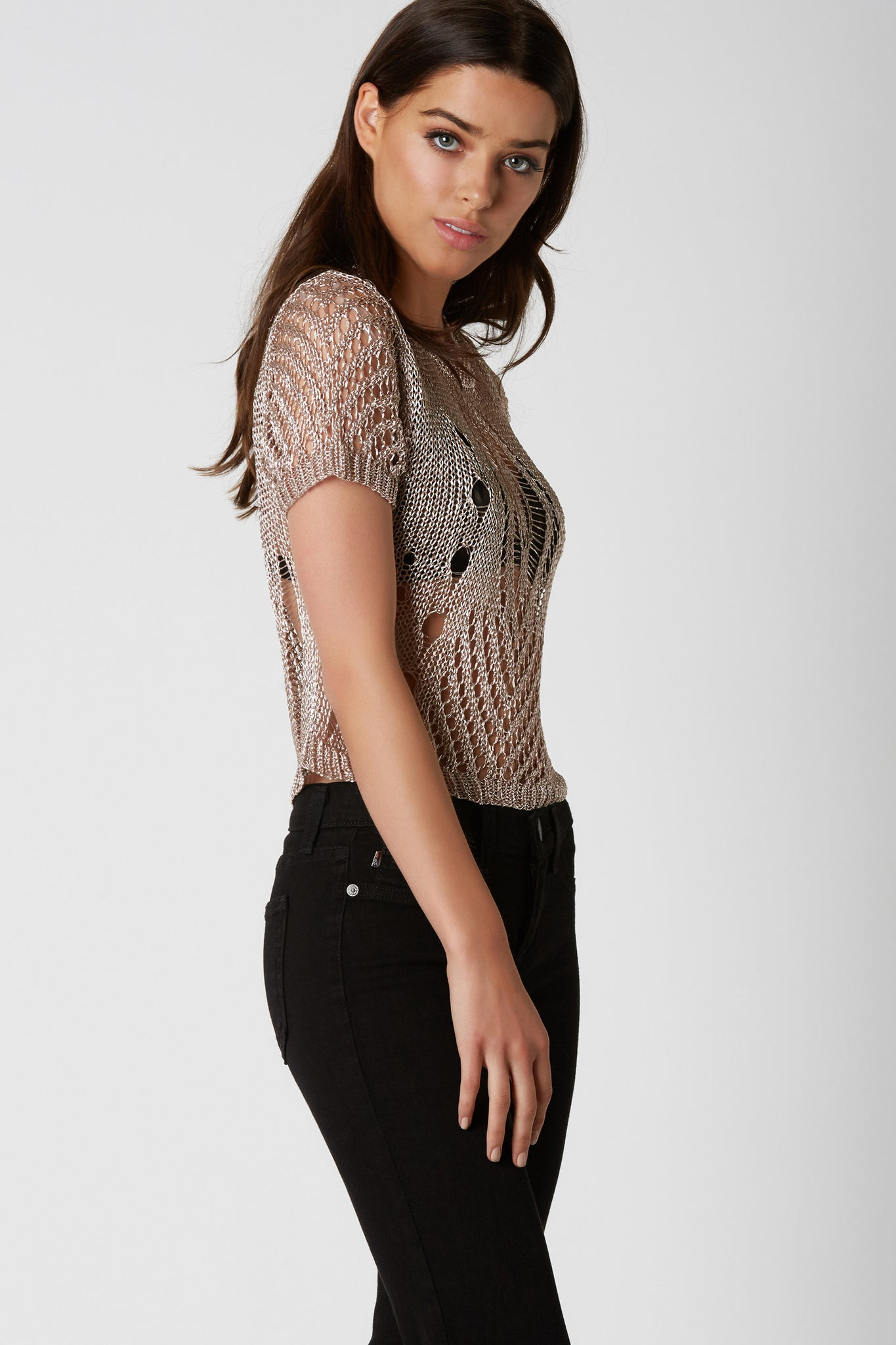 Crew neck loose knit top with short sleeves and straight hem finish. Distressed design and bold metallic finish.