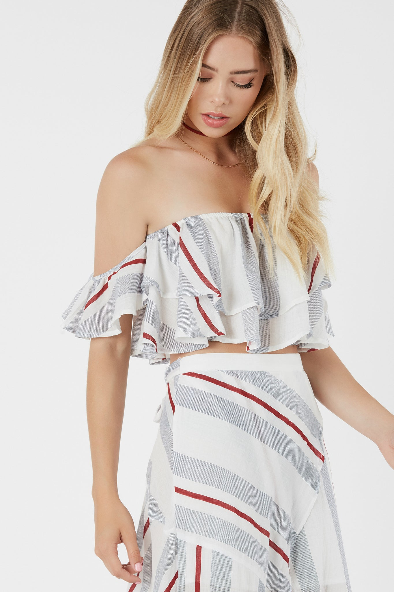 Flirty off shoulder crop top with tiered ruffle design. Stripe patterns throughout with elasticized band for secure fit.