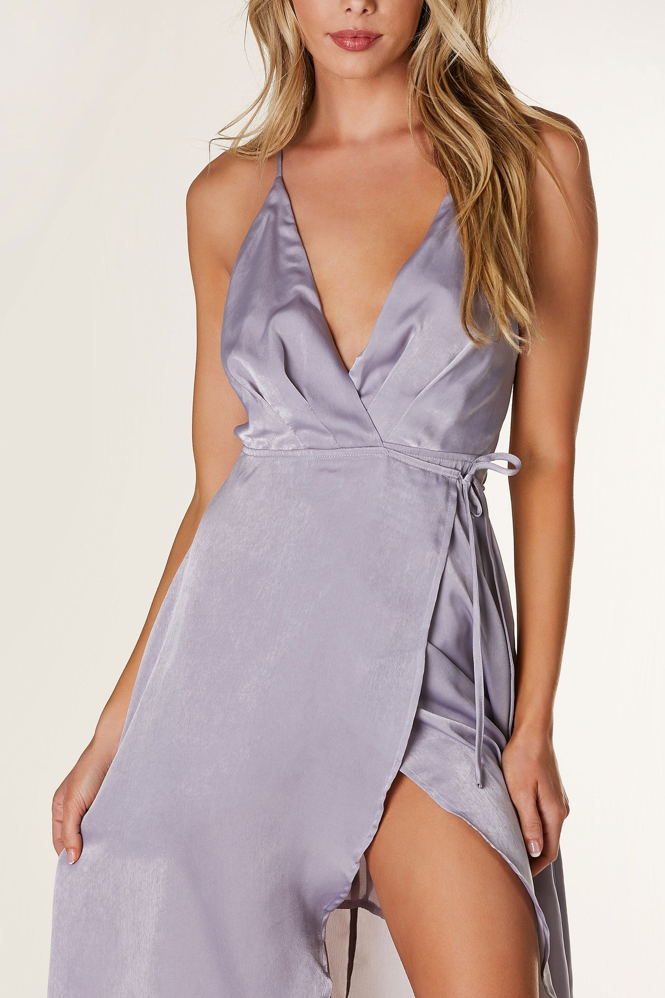 Smooth satin finish wrap dress with chic hi-low hem. Deep V-neckline with adjustable shoulder straps and waist tie closure. Open back with criss-cross strap design and lined body finish.