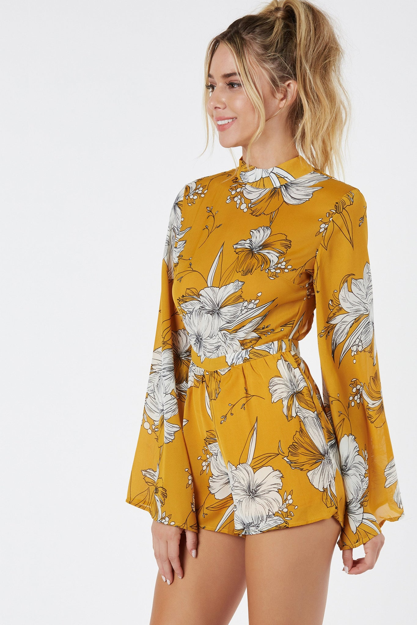 Chic bell sleeve chiffon romper with mock neckline. Floral print throughout with bold open back and ties for closure.