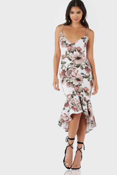 Sleeveless bodycon midi dress with beautiful floral print throughout. Tapered fit with ruffled hi-low hem.