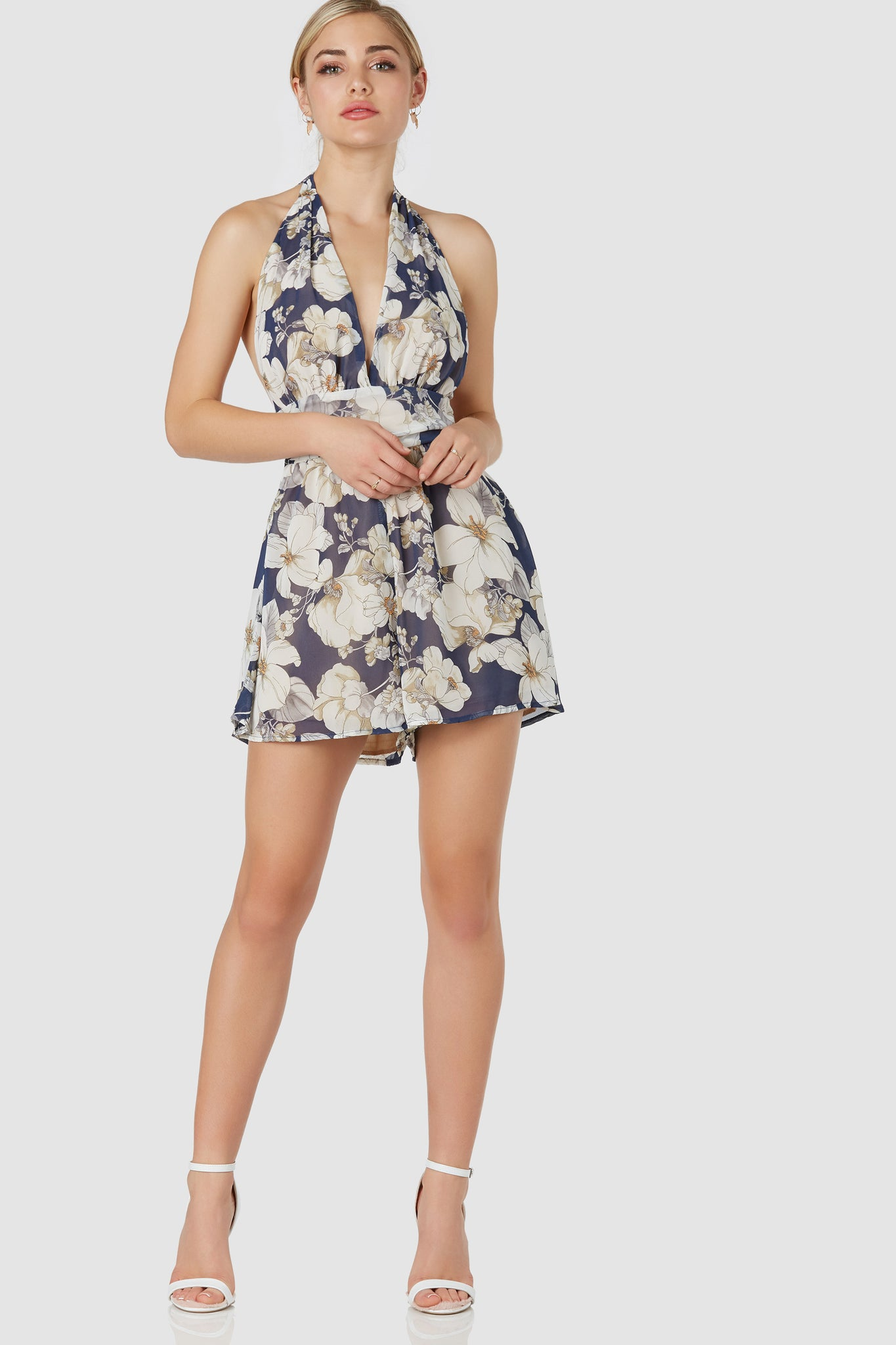 Flattering sleeveless romper with chic halter neckline and open back. Floral print throughout with smooth lining and ties for closure.